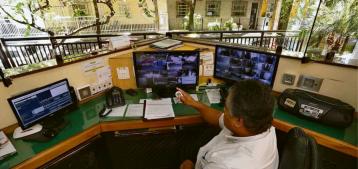 Foto de um porteiro em frente a monitores dentro da portaria de um condomínio para a pauta Ideias para reduzir custos em condomínios para o Blog da Estasa